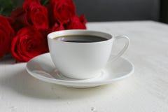 Kaffee und Rosen, Stillleben Schwarzer Kaffee in einer weißen Schale mit einer Untertasse auf dem Tisch, ein Blumenstrauß von rot stockfotos