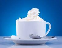 Kaffee und Sahne auf blauem Hintergrund Stockfotografie