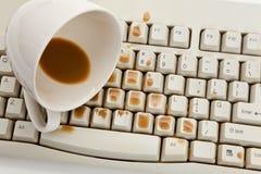 Kaffee und schädigende Computertastatur stockfotos