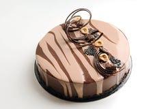 Kaffee- und Schokoladenkuchen mit gewundener Schokoladendekoration und -haselnüssen lizenzfreies stockbild