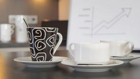 Kaffee- und Teeschalen auf Anrichten vor einer unscharfen Flip-Chart mit kommerziellen Grafiken lizenzfreies stockfoto