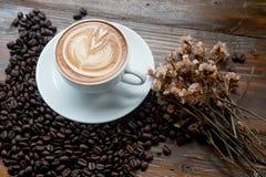 Kaffee und verschüttete Kaffeebohnen mit Trockenblumen Stockfotos