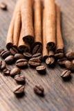 Kaffee und Zimtstangen auf Makrovertikale des hölzernen Hintergrundes lizenzfreie stockfotos