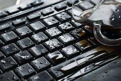 Kaffee verschüttet auf einer schwarzen Tastaturnahaufnahme lizenzfreies stockbild