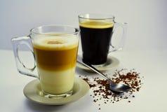 Kaffee weiß und schwarz mit einem Teelöffel und einem verschütteten Kaffee auf dem Stoff Stockfoto