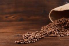 Kaffee wird aus einer Leinwand auf einem hölzernen Hintergrund gegossen Stockfotos