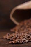 Kaffee wird aus einer Leinwand auf einem hölzernen Hintergrund gegossen Stockfoto