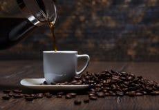 Kaffee wird in eine Schale auf einer Untertasse gegossen Lizenzfreies Stockbild