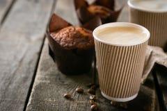Kaffee zum Mitnehmen mit Muffin auf hölzernem Hintergrund lizenzfreie stockbilder