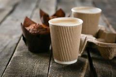 Kaffee zum Mitnehmen mit Muffin auf hölzernem Hintergrund lizenzfreie stockfotos