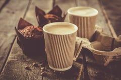 Kaffee zum Mitnehmen mit Muffin auf hölzernem Hintergrund stockfoto