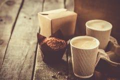 Kaffee zum Mitnehmen mit Muffin auf hölzernem Hintergrund stockfotos