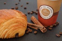 Kaffee zum Mitnehmen und Hörnchen mit Kaffeebohnen lizenzfreie stockbilder