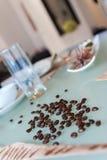 Kaffeebohne auf Glastabelle Stockfotografie