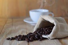 Kaffeebohne in der Tasche auf Holz Lizenzfreie Stockfotos