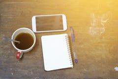 Kaffeebohne, die an einem Handy liegt Lizenzfreies Stockfoto