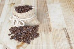 Kaffeebohne in einem Sack auf dem Holztisch Stockfotografie