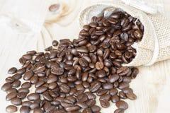 Kaffeebohne in einem Sack auf dem Holztisch Lizenzfreie Stockfotografie