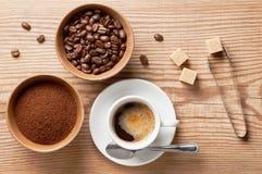 Kaffeebohne-, gemahlenerkaffee und Tasse Kaffee auf Holztisch mit Ausrüstung und Bestandteilen, Draufsicht Stockbild