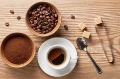 Kaffeebohne-, gemahlenerkaffee und Tasse Kaffee auf Holztisch mit Löffel, Zuckerzange, Rohrzuckerwürfeln und Kaffeebohnen Lizenzfreie Stockbilder