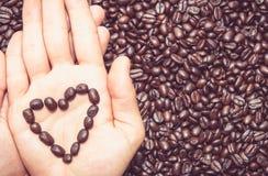 Kaffeebohne-Herzsymbol auf die Hand stockbilder