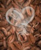 Kaffeebohne mit heißem Dampf in Form einer Herznahaufnahme lizenzfreie stockfotos