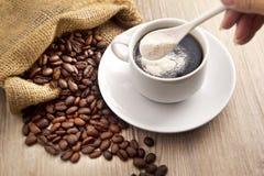 Kaffeebohne und ein Löffelmilchpulver Stockfoto