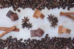 Kaffeebohnehintergrund mit Schokolade, Anis, Karamell und Zimt stockfotos