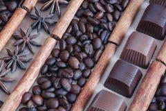 Kaffeebohnehintergrund mit Schokolade, Anisstern und Zimtstangen stockbilder