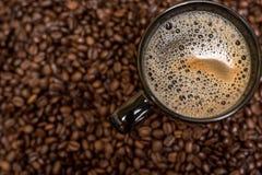 Kaffeebohnehintergrund und schwarze Schale Stockfoto