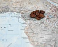Kaffeebohnen auf Afrika-Karte Stockbilder