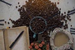 Kaffeebohnen auf alten Uhren Stockbilder