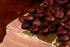 Kaffeebohnen auf Buch Stockfotografie