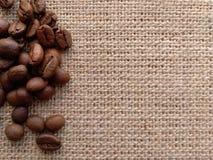 Kaffeebohnen auf byurlap Nutzfläche stockfotografie
