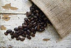 Kaffeebohnen auf dem hölzernen Hintergrund des Schmutzes Lizenzfreie Stockfotografie