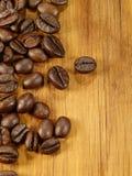 Kaffeebohnen auf dem hölzernen Schreibtisch lizenzfreie stockbilder