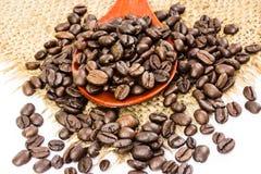 Kaffeebohnen auf dem Rausschmiß und hölzernem Löffel Stockfoto