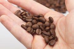 Kaffeebohnen auf den Händen Lizenzfreie Stockfotografie