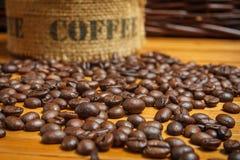 Kaffeebohnen auf der hölzernen Tabelle Stockbilder