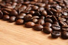 Kaffeebohnen auf einem Holztisch Stockfotografie