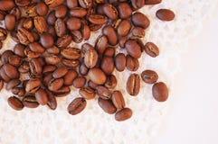 Kaffeebohnen auf einer weißen gestrickten Serviette lizenzfreie stockfotografie