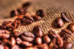 Kaffeebohnen auf grobem Sackzeug Stockfotografie