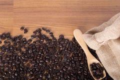 Kaffeebohnen auf hölzernem Löffel mit Leinwand auf Tabellenhintergrund stockfoto
