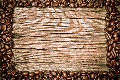 Kaffeebohnen auf hölzerner Beschaffenheit Lizenzfreie Stockfotos