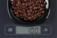 Kaffeebohnen auf Küchenskala Stockfotos
