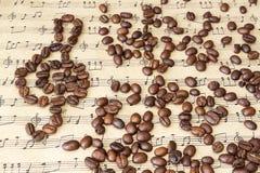 Kaffeebohnen auf Noten Lizenzfreie Stockfotos
