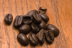 Kaffeebohnen auf rotem Holz Lizenzfreies Stockfoto