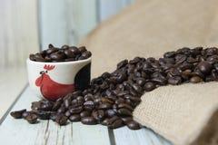 Kaffeebohnen auf Sack und hölzernem Hintergrund, selektiver Fokus (s Stockfoto