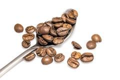 Kaffeebohnen auf silbernem Löffel Stockfotos