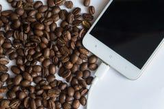 Kaffeebohnen auf weißem Hintergrund mit Smartphone Lizenzfreie Stockbilder